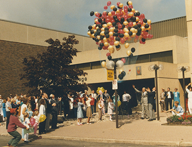 Old photo of students and staff/faculty releasing many balloons