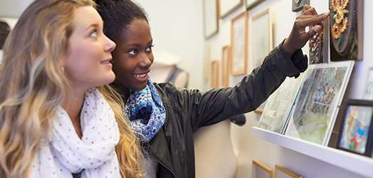 Two people admiring art in a gallery