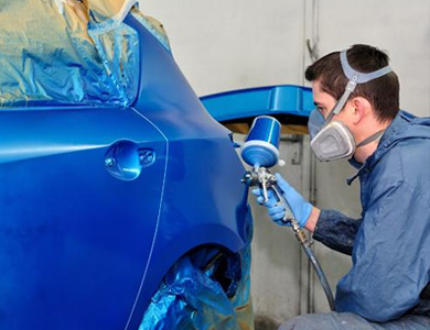 apprentice painting a car