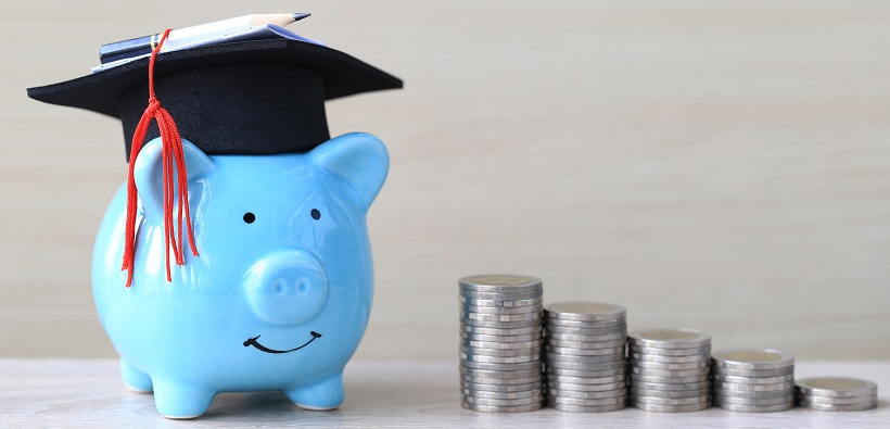 blue piggy bank wearing a graduate cap with coins beside it