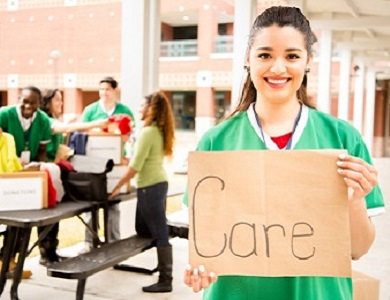 student holding a sign that says care