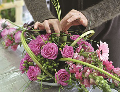 woman's hands creating a pink floral arrangement