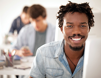 Student smiling at a computer