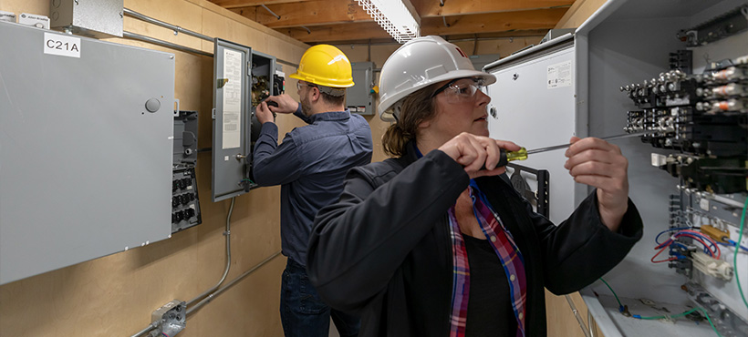 elevator technicians working on an electrical box