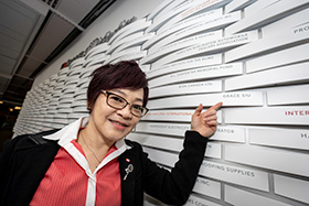 grace siu in front of donor wall
