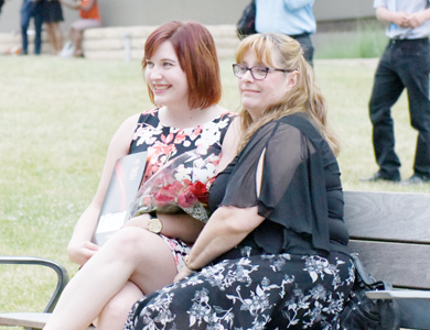 Parent and Student sitting on a bench smiling