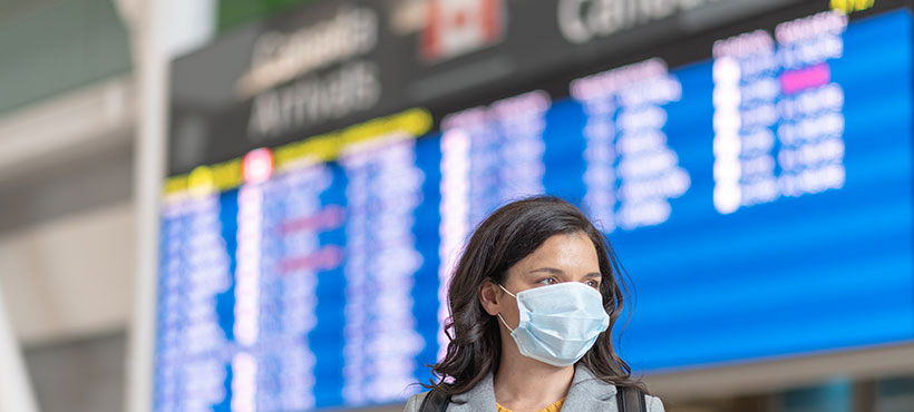 Woman at Canadian airport with luggage wearing face mask