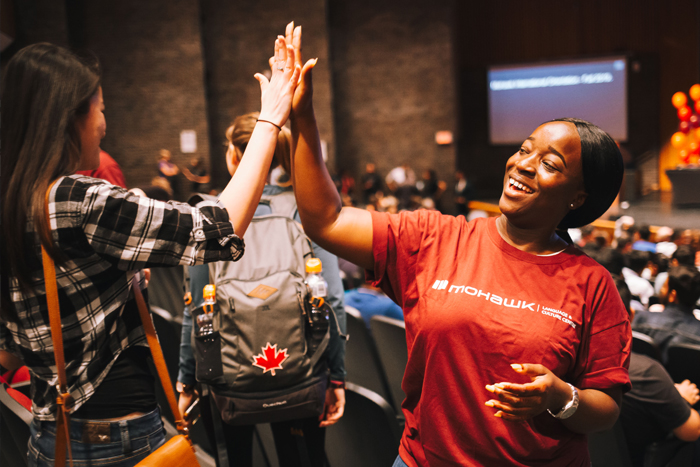 A volunteer greets an orientation attendee with a high five