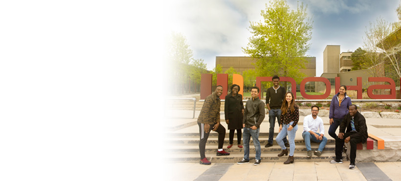 Group photo of students by the Mohawk sign at Fennell Campus