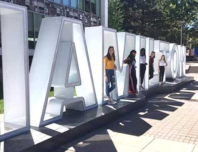 Students standing in the Hamilton sign