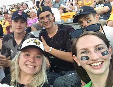 5 students in the stands of a Hamilton Tiger Cats football game