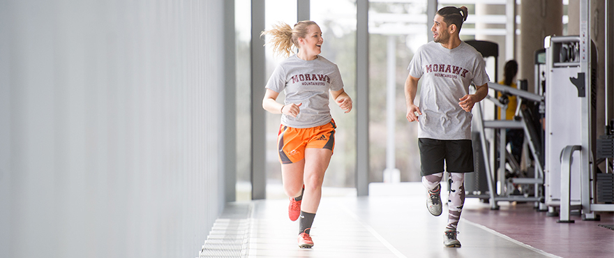 Two students running in the David Braley Athletics and Recreation Centre