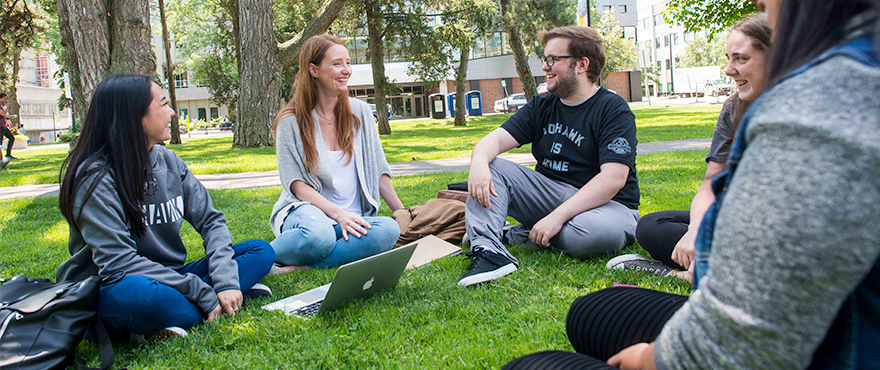 Mohawk students sitting and talking on the grass