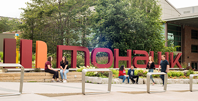 Students sitting and walking by the sign at the entrance to Mohawk College's Fennell Campus