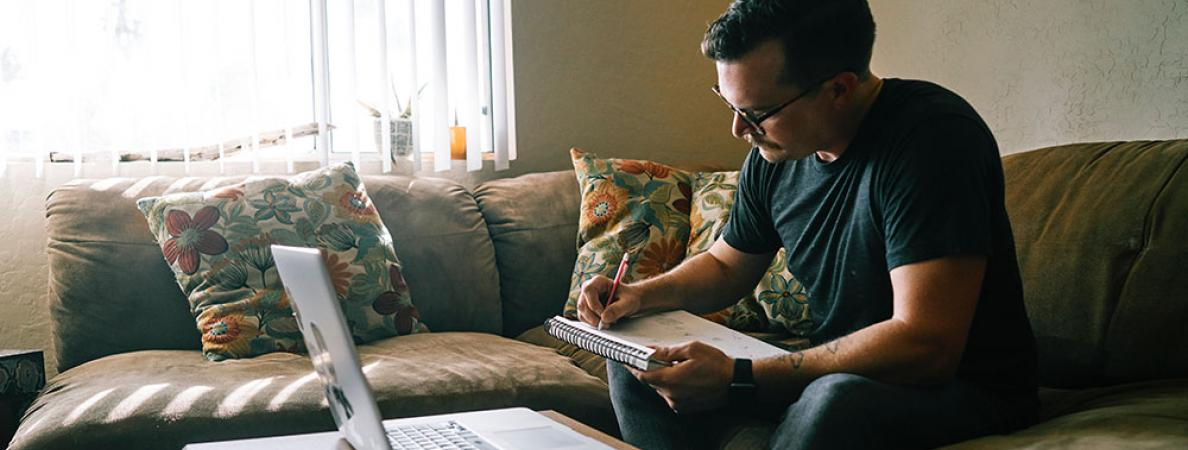 white male taking notes while sitting on couch with laptop open