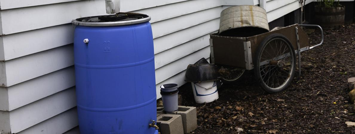 blue rain barrel against house