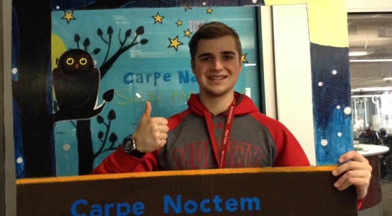 Student taking a selfie with the Carpe Noctem cut out frame