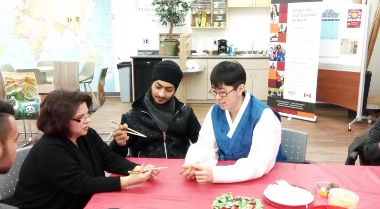 One Student teaching other students how to eat through a chopstick in Coffe Club Session