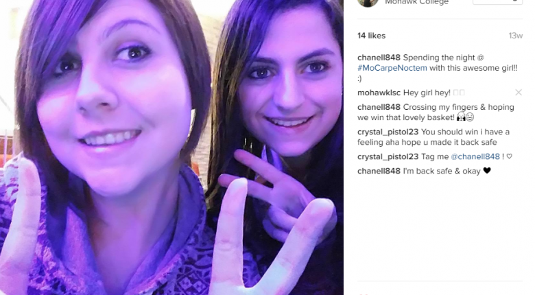 Two female students posting about Carpe Noctem on social media