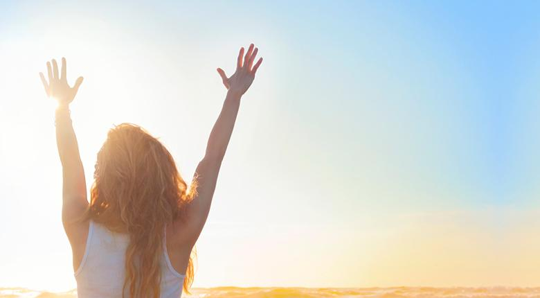 Woman near the water watching sun rise while raising her hands up to the sky