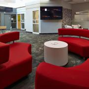 The Agency Interior three red couch with circle table in between