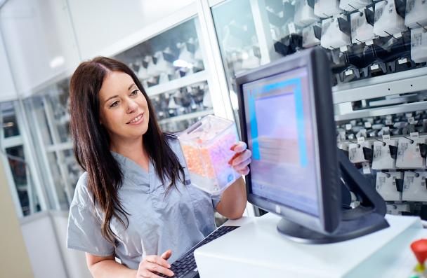 female pharmacy technician reviewing container of drugs standing beside computer