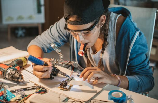 female late teens or early 20s working on soldering metal and wires while sitting at table.