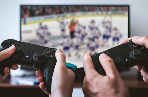 two people playing a hockey video game.