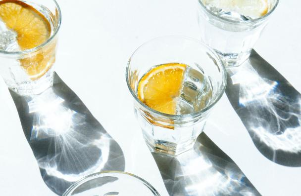 5 glasses of water with slices of oranges seen from above