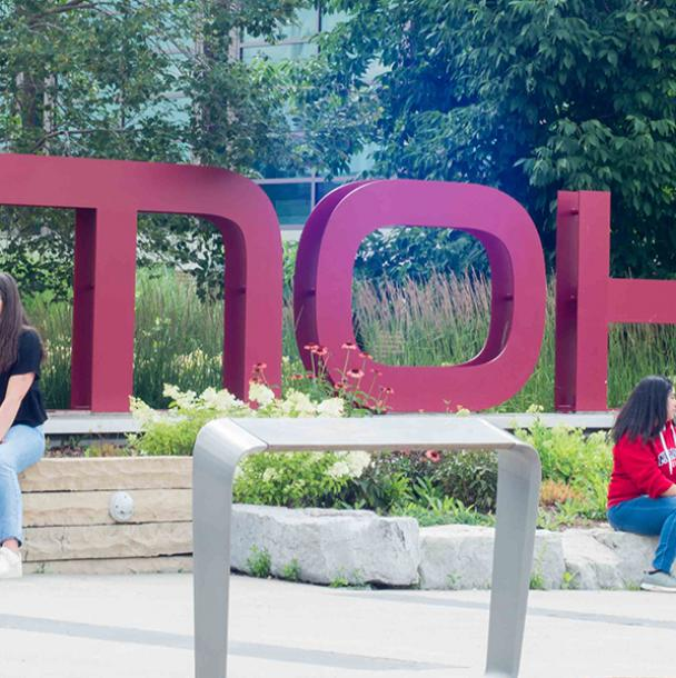 Students walking in front of the Mohawk College sign