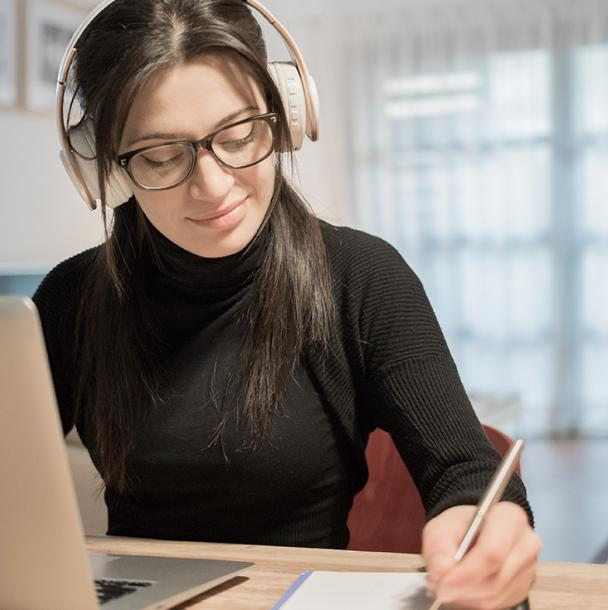 Student wearing headphones working at home on a laptop
