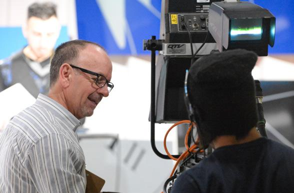 Broadcasting instructor assisting student with camera work