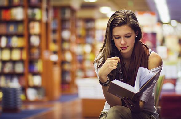 General Arts and Sciences student reading a book in a library.