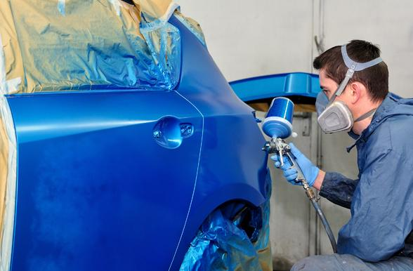 Student fixing a body parts of a car.