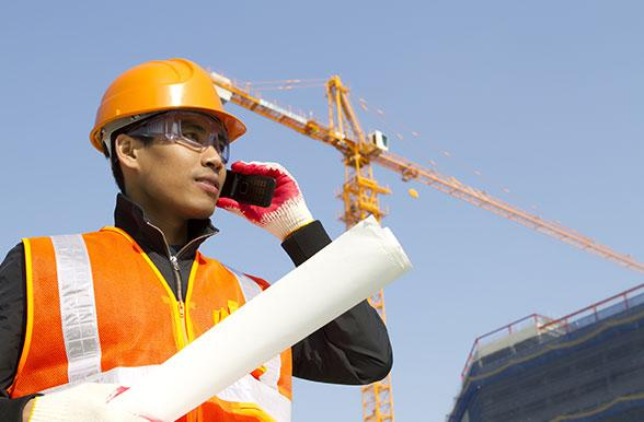 civil engineering technician student on the phone with a crane in the background