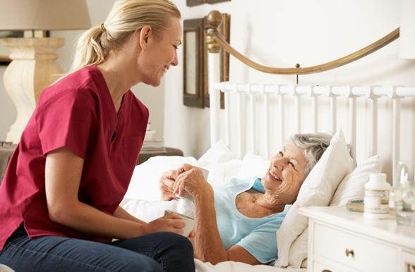 Student talking to senior women patient in bed