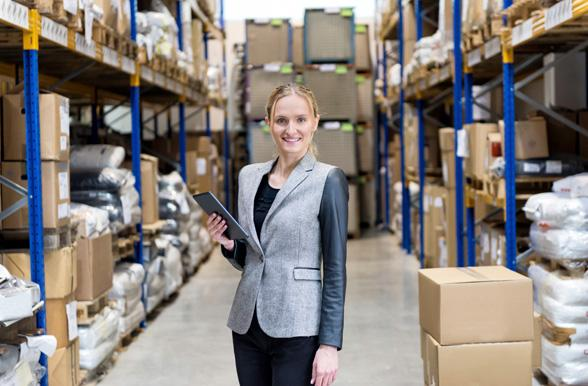 Businesswoman holding tablet and smiling in warehouse