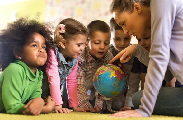 group of children at preschool examining world globe with their teacher