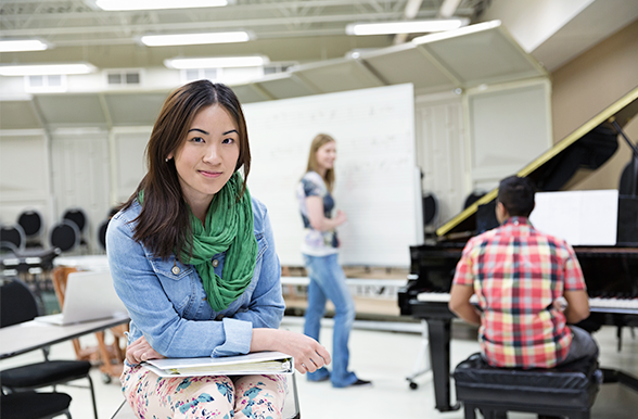 Applied Music Preparatory student sitting and smiling with a binder