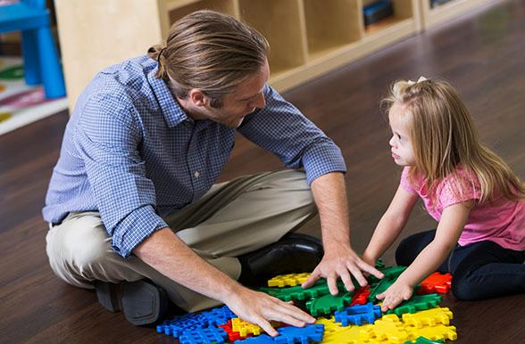 Early Childhood Educator puts puzzle together on floor with child