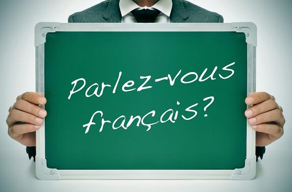 Person holding sign with Parlez-vous francais written