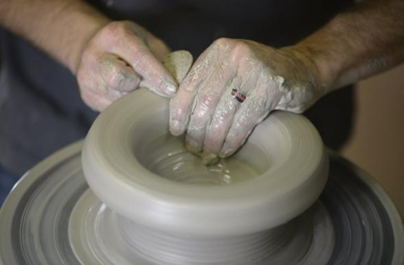 Clay being worked into bowl on pottery wheel