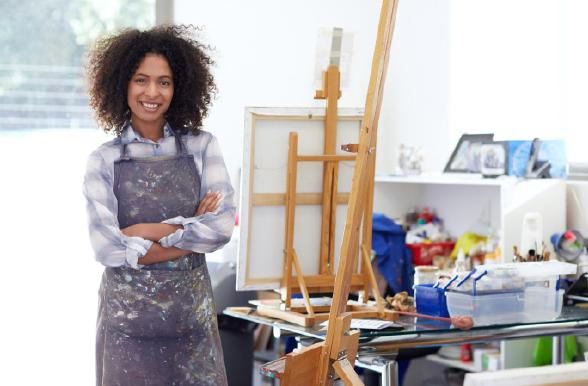 Student posing and smiling in front of an easel