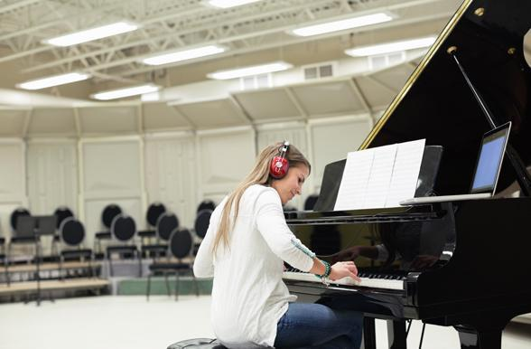 Student playing a grand piano