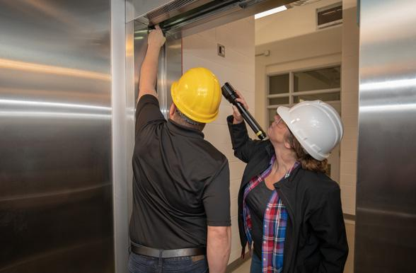skilled trades professionals inspecting an elevator door